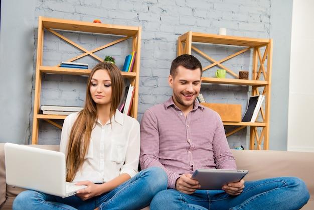 ラップトップとタブレットに取り組んでいる幸せな心の男性と女性