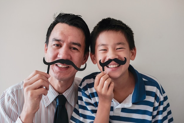 Happy mixed father and preteen son having fun with fake mustache