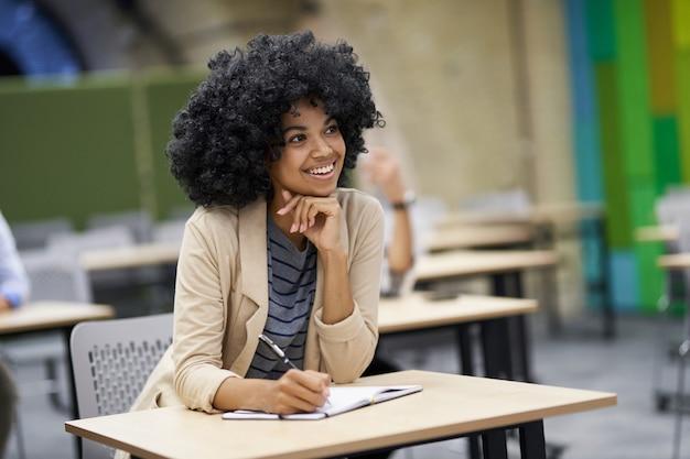 Счастливая бизнесвумен смешанной расы сидит за столом в современном коворкинге и слушает тренера