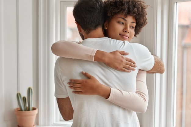 Happy mixed race couple embrace each other, express support and love, have friendly relationships, pose near window in living room, enjoy togetherness. diverse boyfriend and girlfriend hug indoor