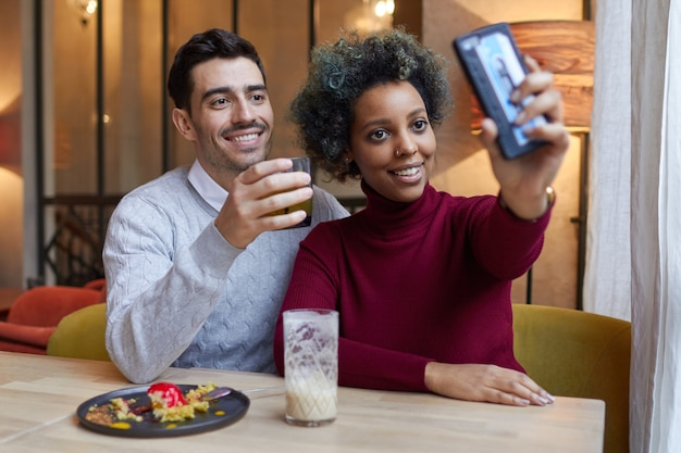 Счастливая пара смешанной расы, делающая селфи с телефоном в кафе