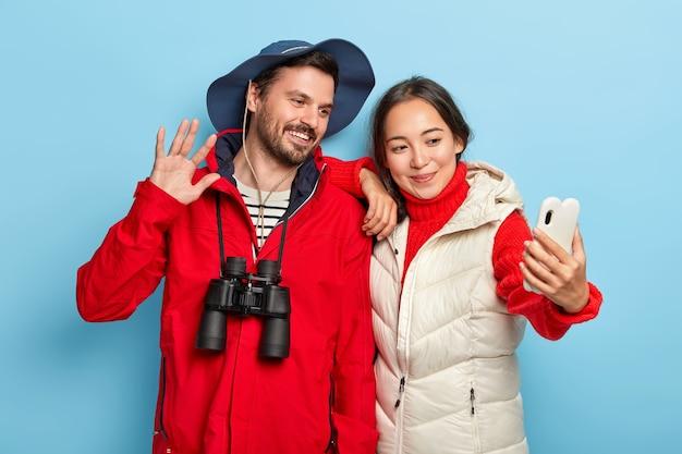 행복한 혼혈 커플이 스마트 폰으로 셀카를 찍고, 트레킹 여행을 즐기고, 서로 가까이 서 있고, 캐주얼 한 옷을 입고, 쌍안경을 사용합니다.
