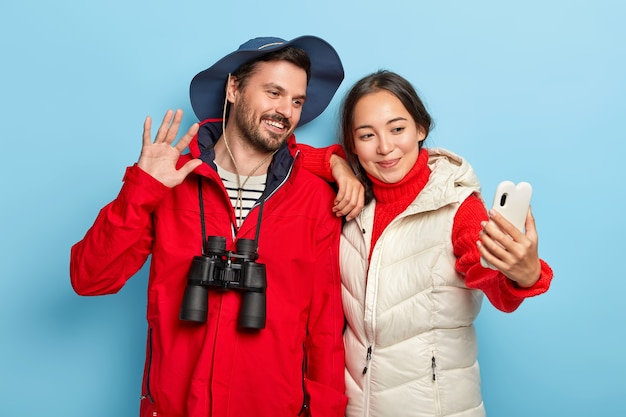 Happy mixed race couple take selfie on smartphone, enjoy trekking journey, stand closely to each other, dressed in casual wear, use binoculars