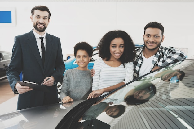 Happy mixed race family and agent near new auto.
