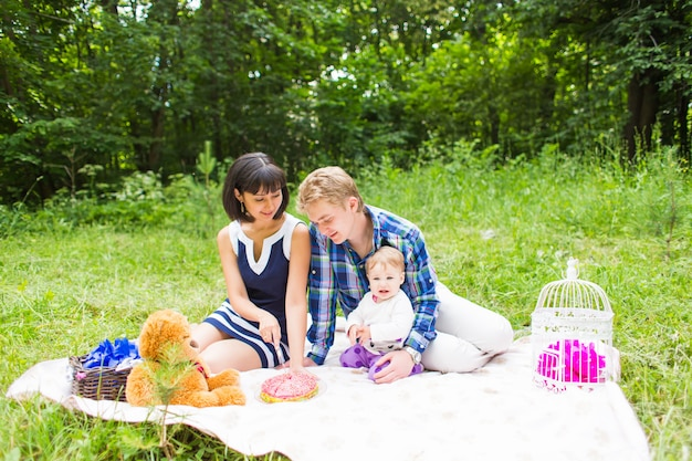 Happy mixed race family having a picnic and playing in the park.