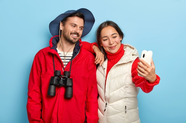 Happy mixed race lovely couple with glad expressions, take selfie on smartphone camera, spend vacation together, dressed casually, use binoculars