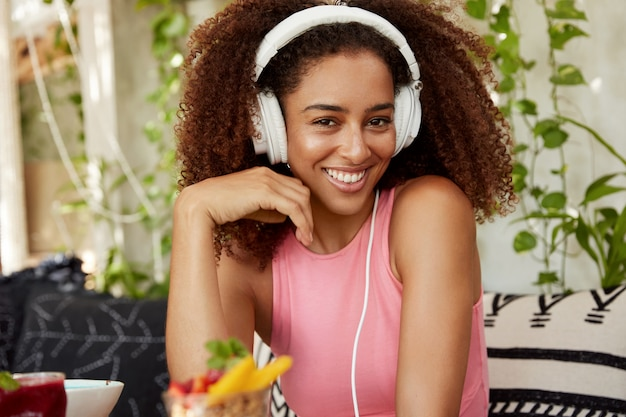 Happy mixed race teenage girl with curly hairstyle glad to listen music or radio in headphones, has long awaited vacations, sits on comfortable sofa with dessert. female blogger enjoys melody
