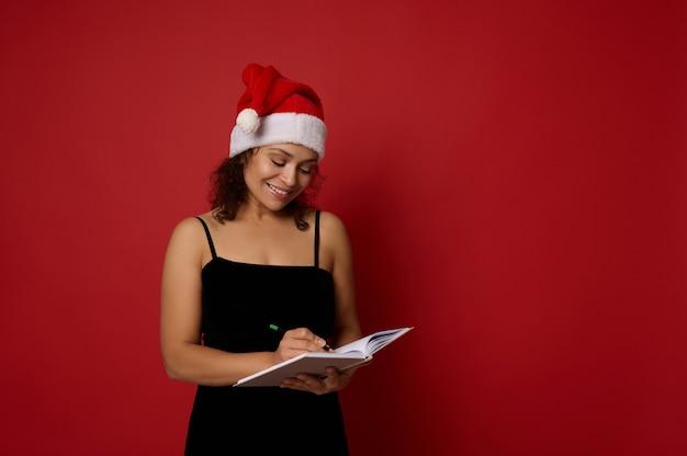 산타 모자를 쓴 행복한 혼혈 여성, 메모장에 쓴 미소, 새해에 할 일 목록. 텍스트 및 광고를 위한 복사 공간이 있는 빨간색 배경의 크리스마스 및 새해 개념