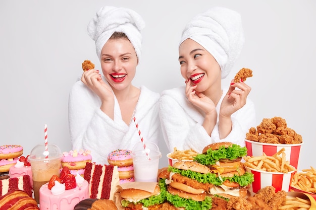 Happy mixed race young women look gladfully at each other eat junk food hold nuggets have tasty dinner
