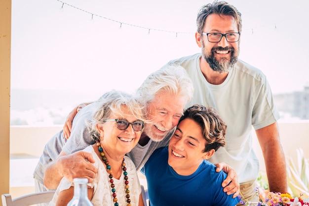 幸せな混合3世代家族が抱き合って一緒に楽しむ-人々は老人の大人とティーンエイジャーと一緒に肖像画をグループ化します-明るい空の背景と陽気な笑顔