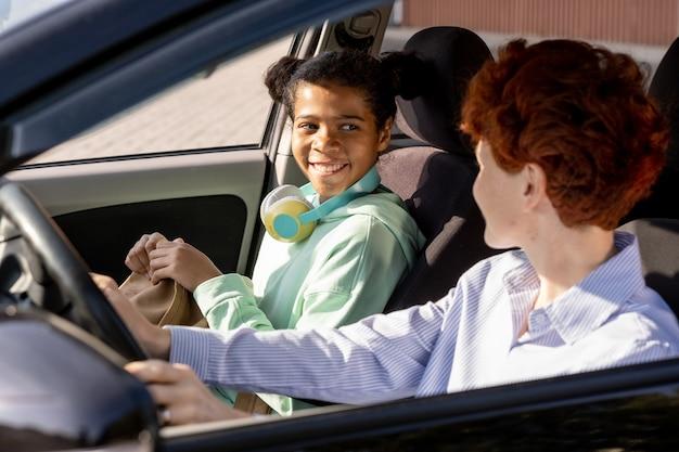 차 안에서 젊은 여성을 바라보는 행복한 혼혈 소녀