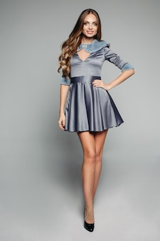 Happy model in fashionable grey dress with fur collar and sleeves.