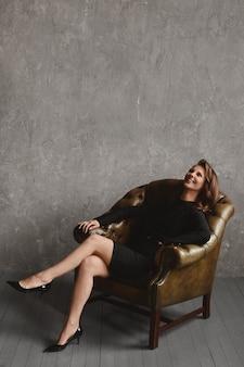 Счастливая модельная девушка с длинными стройными ногами в черном платье, сидящая в винтажном кожаном кресле на винтажном и потрепанном фоне