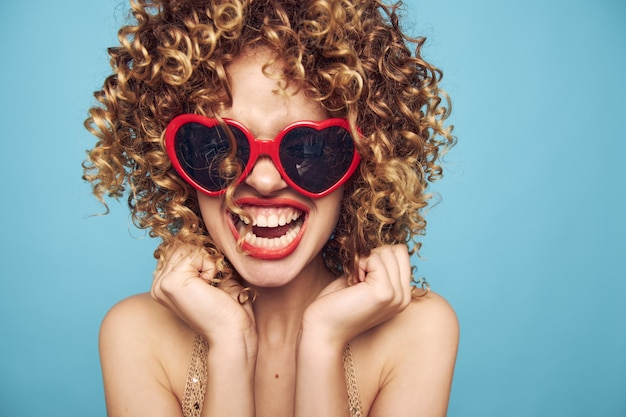 Happy model hand gestures on a blue background, red sunglasses