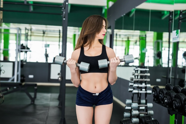 Happy model with brunette hair is doing exercises in sportclub dressed up in black sportswear
