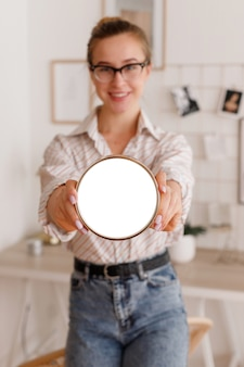 Happy model with clock mockup in office