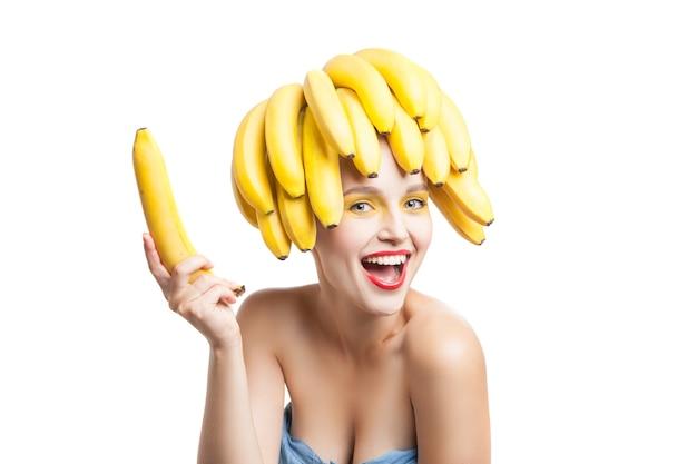 Счастливая модель с косметикой и связкой бананов на голове, держащейся в руке и смотрящей в камеру.