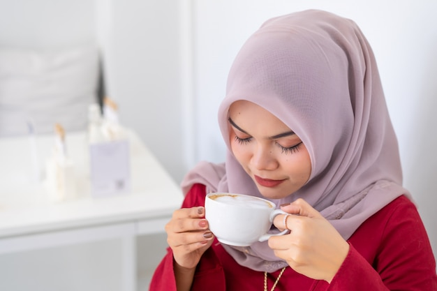 Happy modern asian muslim business woman working on desk smelling coffee.