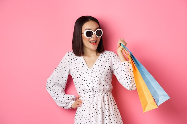 행복 한 현대 아시아 여자 쇼핑몰에서 쇼핑, 옷 가방을 들고 웃 고, 선글라스를 쓰고, 핑크 위에 서