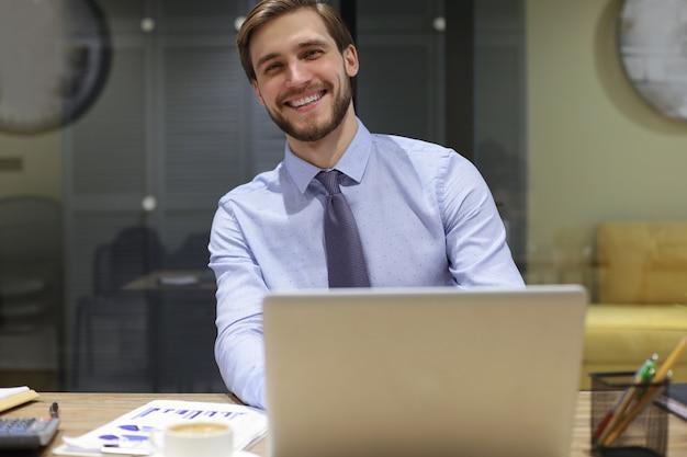 Счастливый современный деловой человек, работающий с помощью ноутбука, сидя в офисе.