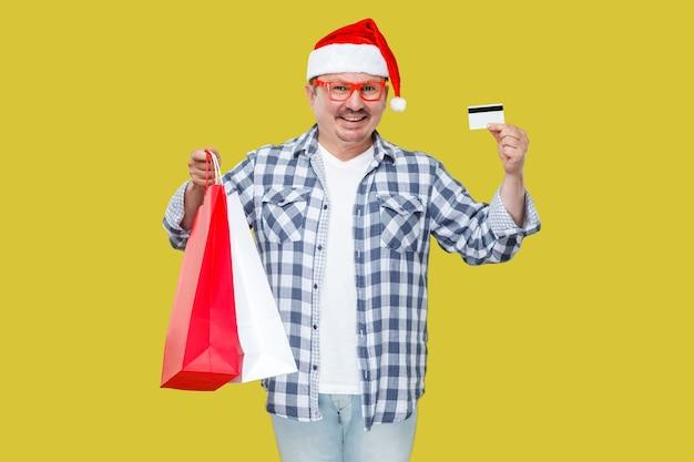 Счастливый современный случайный человек средних лет в красной новогодней шапке, очках, стоя и держа подарочные пакеты для покупок и кредитную карту с зубастой улыбкой, глядя в камеру. изолированные на желтом фоне