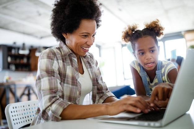 コンピューターで作業している自宅で幸せな現代家族の母と子の娘