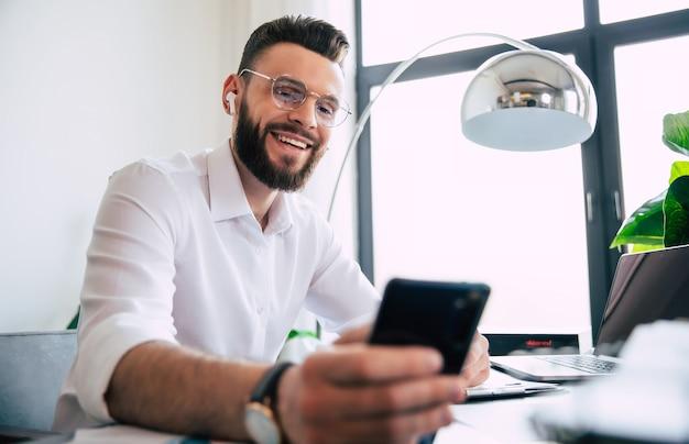 Счастливый современный красивый стильный бородатый бизнесмен в очках и белой рубашке работает над ноутбуком и смерт-телефоном на столе офисного рабочего места.