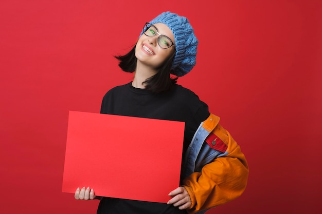 Happy modern teenage woman in colorful jacket and glasses showing empty red placard