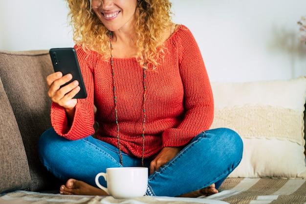 幸せな現代の女性はソファで自宅でビデオ電話を楽しんでいます