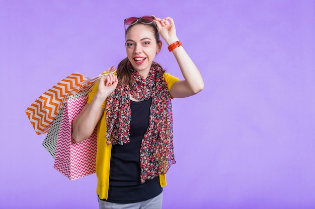 Happy modern woman holding decorative paper bag in front of purple wall