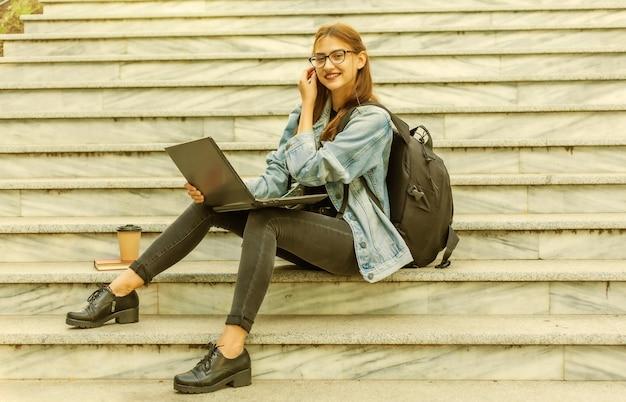 Счастливый современный студент женщины в джинсовой куртке и рюкзаке сидя на лестнице с внешним компьтер-книжкой. дистанционное обучение. современная молодежная концепция.