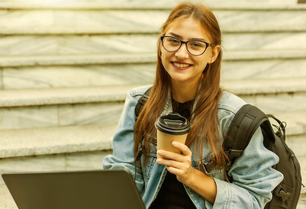Счастливый современный студент женщины в джинсовой куртке и рюкзаке сидя на лестнице с внешним компьтер-книжкой. пьет кофе. дистанционное обучение. современная молодежная концепция.
