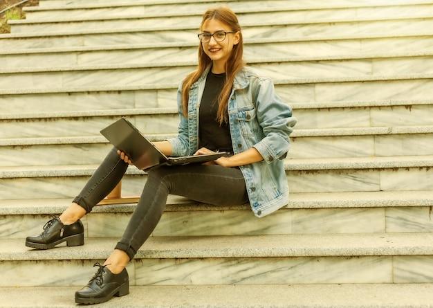 Счастливый современный студент женщины в джинсовой куртке, сидя на лестнице с ноутбуком. дистанционное обучение. современная молодежная концепция.