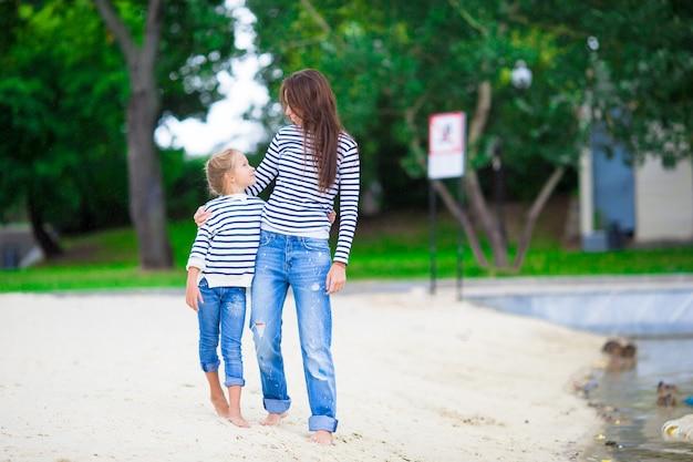 Happy mom and adorable little girl enjoying