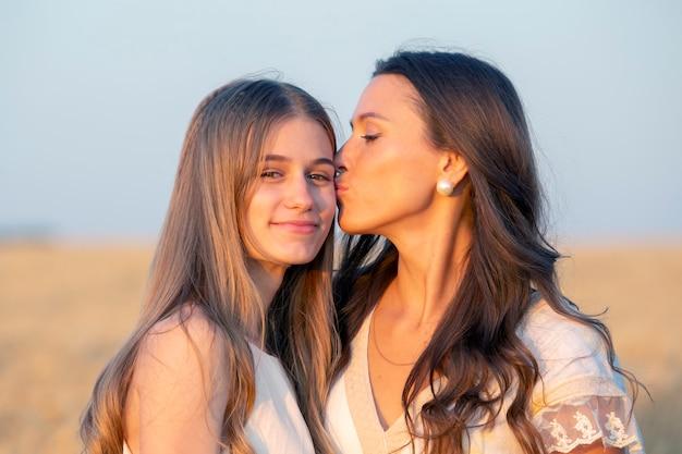 Счастливая мама и взрослая дочь стоят вместе возле пшеничного поля в свете вечернего солнца