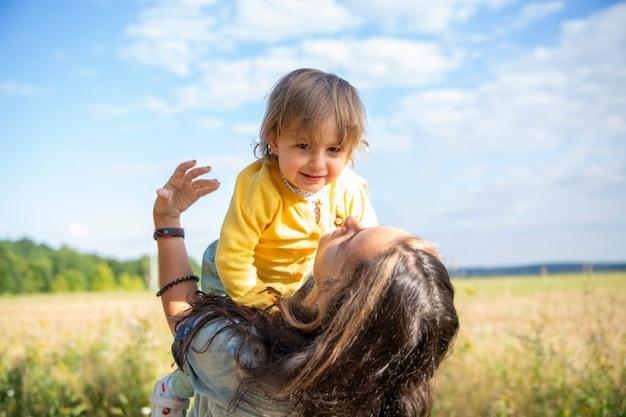 幸せなママと赤ちゃんは、晴れた夏の日の夏にフィールドで遊ぶ