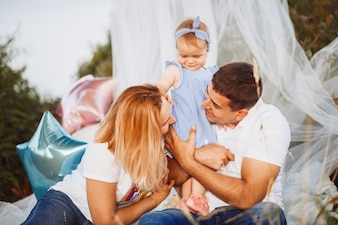 Happy mom and dad hold little daughter on their arms sitting under white tent