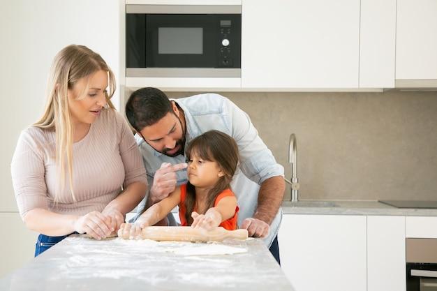 幸せなママとパパが一緒に焼きながら女の子に顔を染める。