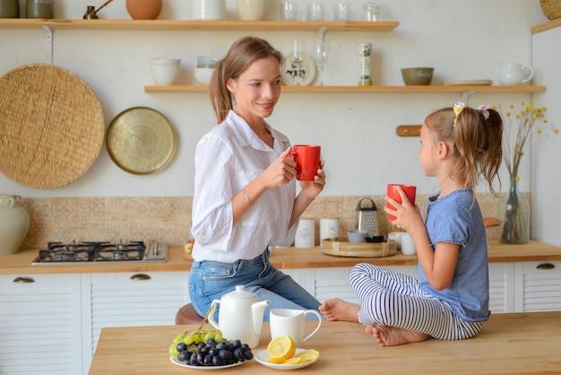 幸せなママと娘が一緒に朝食を作って食べる