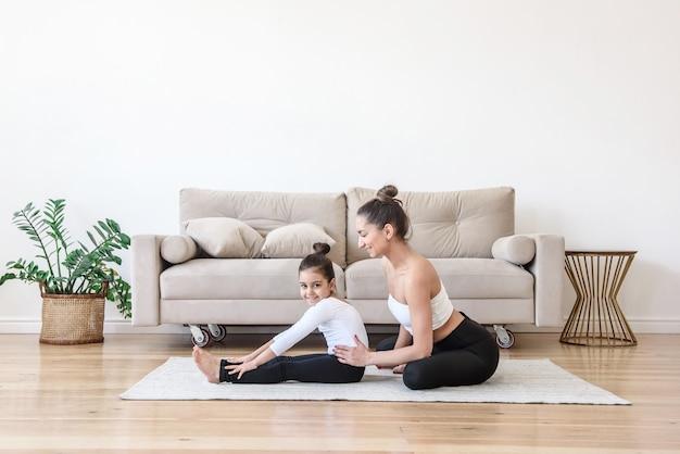 Счастливая мама и дочь вместе занимаются гимнастикой на растяжку дома