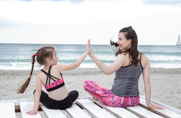 スポーツウェアの幸せな母と娘は海岸でヨガを練習します。家族の価値観と健康的なライフスタイル。