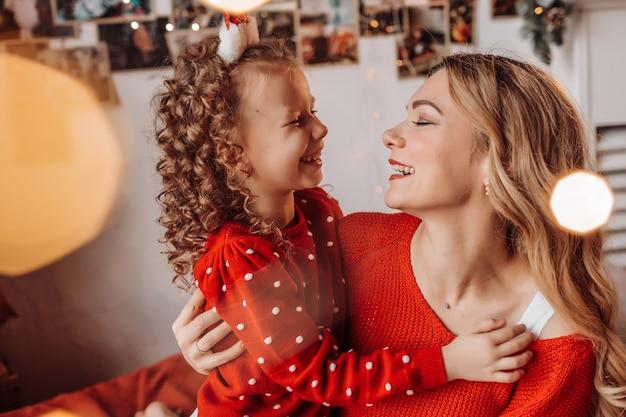 행복한 엄마와 딸이 크리스마스 트리로 집에서 새해를 기대하고 있습니다.