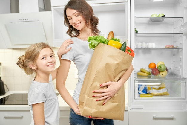 Счастливая мама и дочь позирует с бумажный мешок с продуктами.