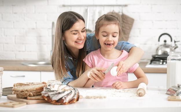 행복한 엄마와 딸이 밝은 부엌에서 수제 케이크를 준비합니다.