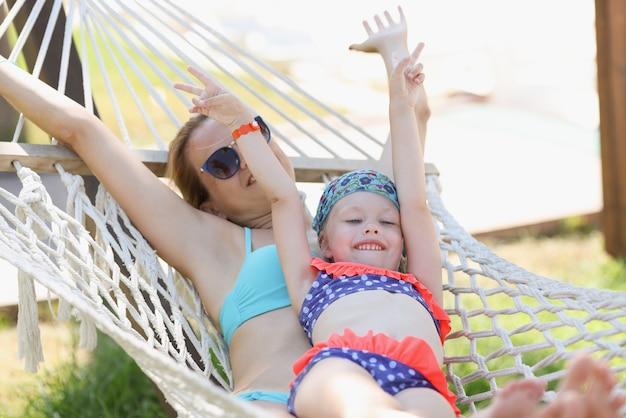 행복한 엄마와 딸이 해먹에 수영복을 타고