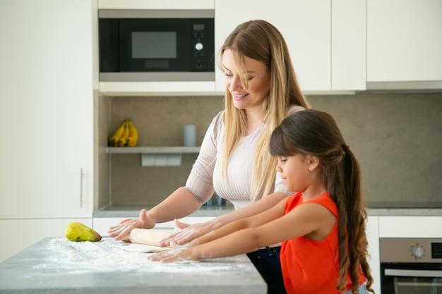 幸せなママと娘のキッチンテーブルの上に生地を圧延します。少女と母親が一緒にパンやケーキを焼きます。ミディアムショット、側面図。家族の料理のコンセプト