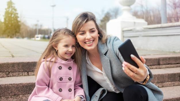 幸せなママと娘が屋外で自分撮りを撮る