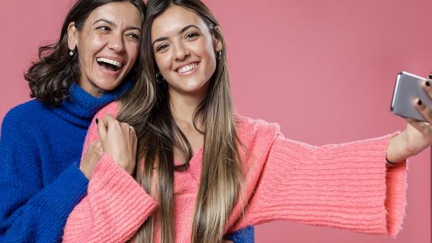 Счастливая мама и дочь, принимая селфи