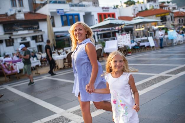 행복한 엄마와 딸이 터키 마르마리스의 산책로를 따라 걷고 있습니다.