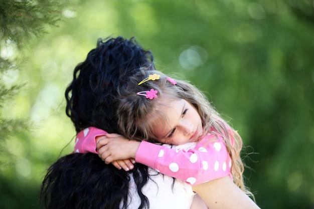 幸せな母と娘。緑豊かな公園を歩く